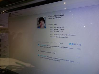 The contact activity view of Unify's Project Ansible unified communications service adapts to the screen on which it is displayed. Seen here is a picture of a demo of the PC version on Unify's stand at Cebit 2014 in Hanover, Germany, showing more information than the iPhone version and, faintly visible on the left, a sidebar with recent project activity notifications.