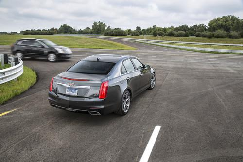 A 2015 Cadillac CTS with V2V technology notifies the driver of the approaching car before the driver can see the vehicle.