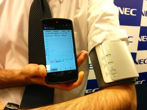 An NEC researcher shows off a wearable blood pressure prototype in Tokyo on Wednesday. The smartphne-linked device squeezes less than conventional cuffs but can still take accurate readings, according to the company.