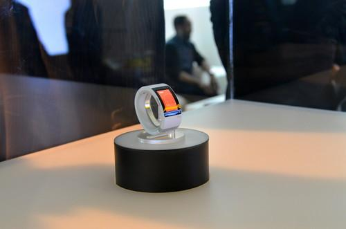 Will.i.am's new Puls smartwatch, with a blurred Will.i.am in the background.
