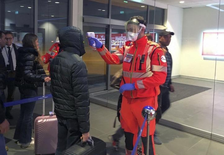 Italian officials vet passengers at Bologna airport.