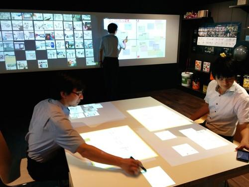 Fujitsu staffers demonstrate a digital brainstorming system in Tokyo on August 6, 2015, sending projected sticky notes from the table to the wall in the background.
