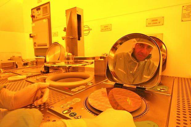 The reflection of Roland Germann, manager of IBM's Nanotechnology Center Operations at IBM Research Zurich, is seen in a silicon wafer. Credit: IBM