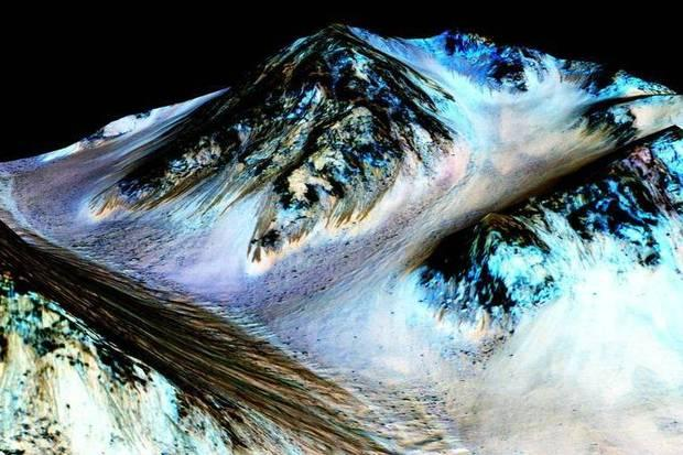 Scientists say the dark,100 meter-long streaks, called recurring slope lineae, flowing downhill on Mars may have been formed by flowing water. The blue colour seen above the dark streaks is unlikely to be related to their formation, but instead are from the presence of the mineral pyroxene.  Credit: NASA/JPL/University of Arizona