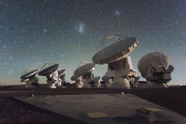Antennas of the Atacama Large Millimeter/submillimeter Array (ALMA), on the Chajnantor Plateau in the Chilean Andes. The Large and Small Magellanic Clouds, two companion galaxies to our own Milky Way galaxy, can be seen as bright smudges in the night sky, in the centre of the photograph. The ALMA Array is also a part of the Event Horizon Telescope project. Credit: ESO/C. Malin