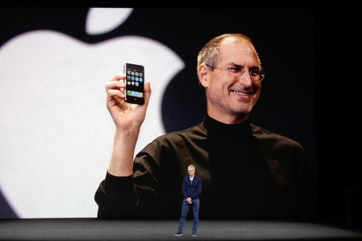 Tim Cook, current Apple CEO, stands before an image of Steve Jobs.