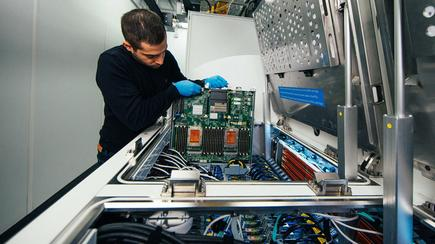 Ioannis Manousakis, a principal software engineer with Azure, removes a server blade from a two-phase immersion cooling tank at a Microsoft data centre.